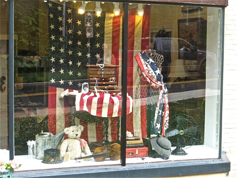 This window display seems to be accessorised with the most patriotic stuffs like a flag, a chair with flag and a dress in tone with Independence Day.