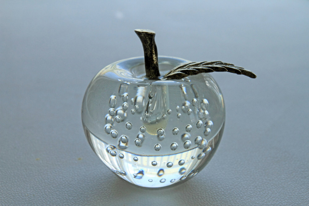 In a shape of an apple, this is a creative transparent glass, made for a jewelry ring holder.