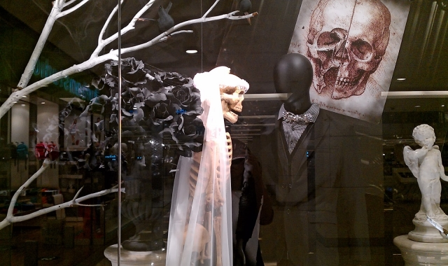 You can see in this window display from Bangkok a nice decoration for Halloween with a dead bride, big black roses, a groom and a sketch of a skull in the background.