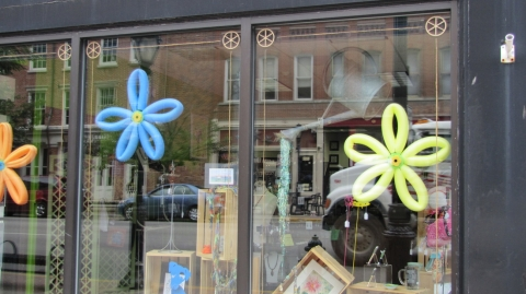 This store is celebrating summer with some balloons transformed into flowers for decorating their window display.