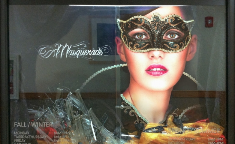 Cat woman or witch? This Halloween window display chose a poster with a beautiful, mysterious woman with a mask and let you pick which character you want.