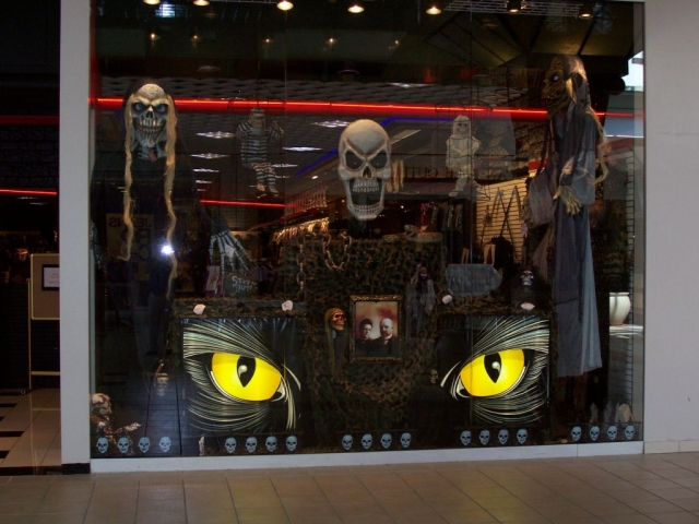 What is standing out a mile in this picture are those yellow eyes, which are surely belonging to a black cat. This kind of window display is fitting perfectly for Halloween.