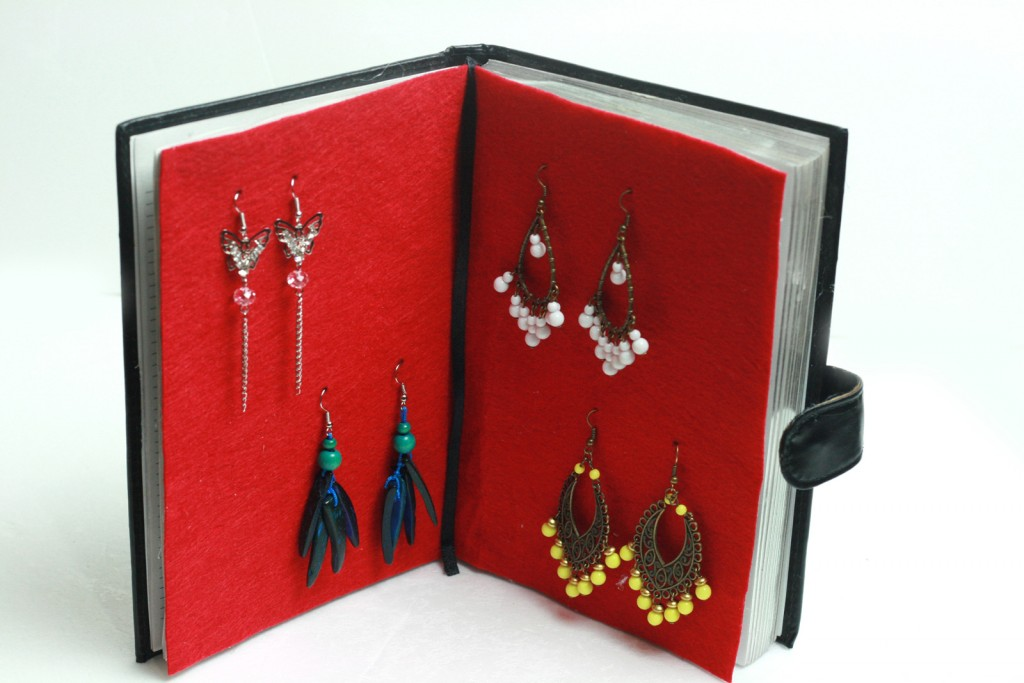 A creative book, metamorphosed into a jewelry earring holder with a little help from a piece of red fabric bound on a page.