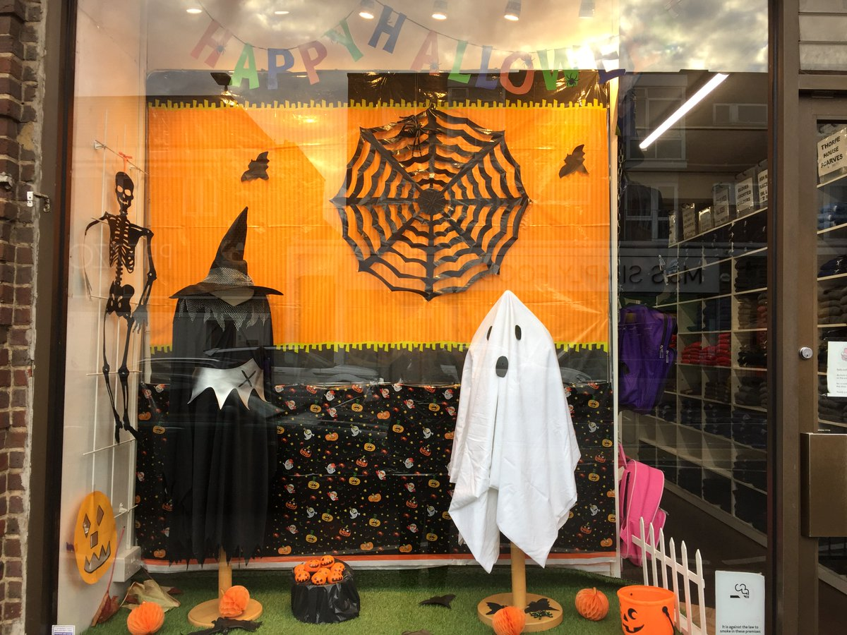 An orange background with a black spiderweb made out of paper and a witch costume followed by a ghost costume, are looking enough in theme for a Halloween window display.