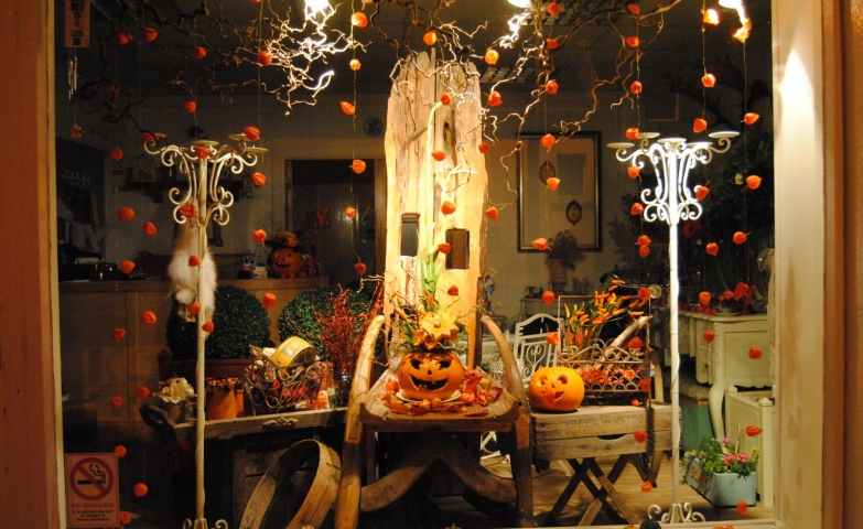This window display decorated for autumn has fallen leaves, two carved pumpkins, and another little autumn details.