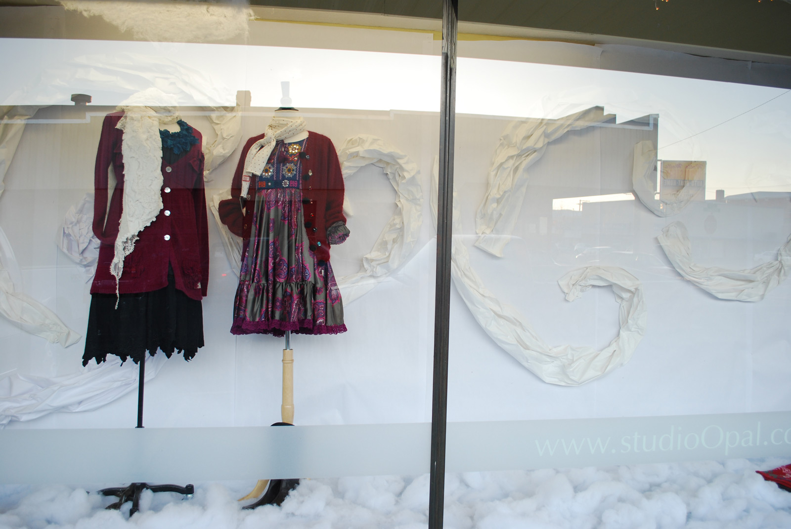 A dark red blemish and other colors, standing out in the lightened window display prepared for winter with the white background and the snow on the ground.