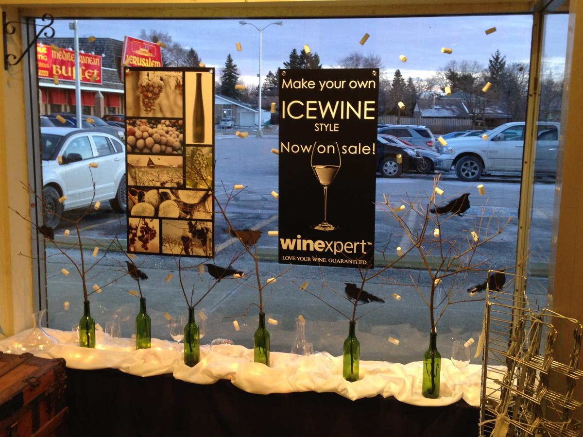 Iced bottles of wine are placed in the window display, on a snow of white fabric as a winter decoration.