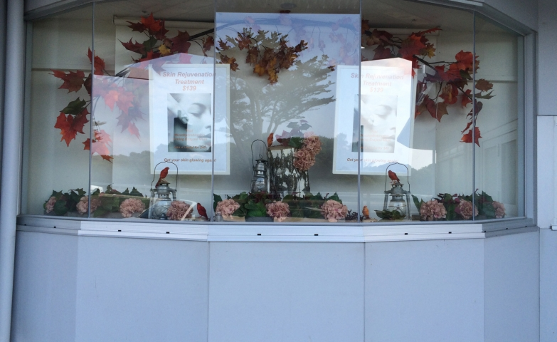 This is a classic concept with autumn leaves and flowers decorating a window display.