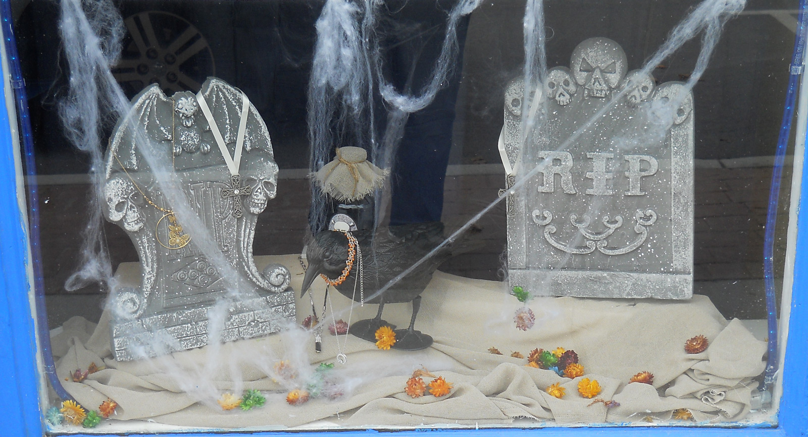 Crypts constructed in a chic way, a raven and fog made out of cotton put on the Halloween window display.