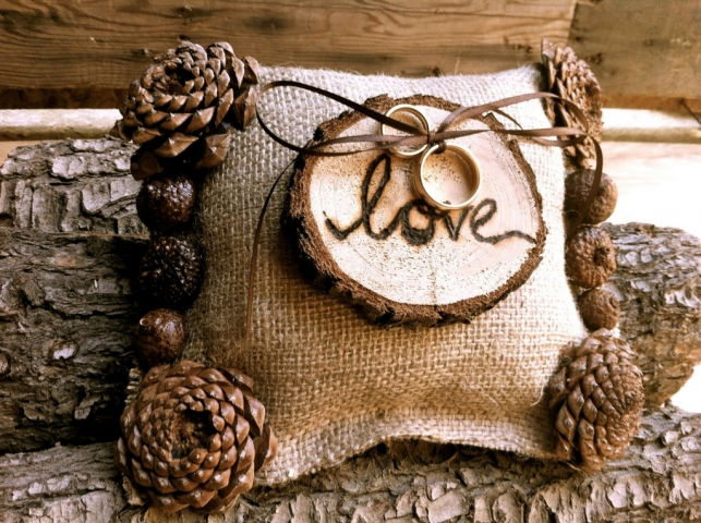 """On a pillow there is bound a piece of wood inscribed with the word """"Love"""". On the borders of the pillow are bound cones. This might be another creative jewelry holder for wedding rings."""