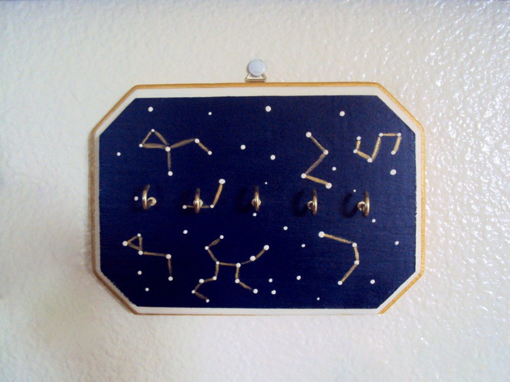 Bring the constellation into your home with this creative jewelry necklace holder made from wood and hooks.