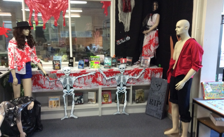 Inside of a window display is a scene for Halloween, full of blood on the table, on the clothes of the mannequins and on the window.