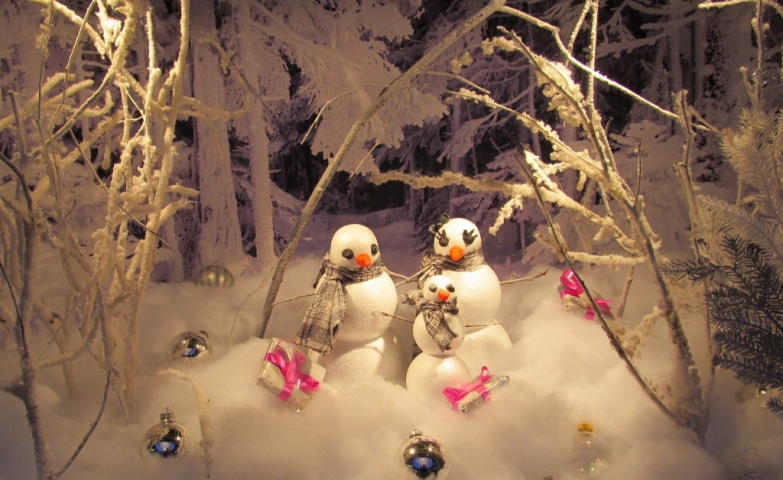 A winter window display showing us a family of snowmen enjoying the presents and the big snow.