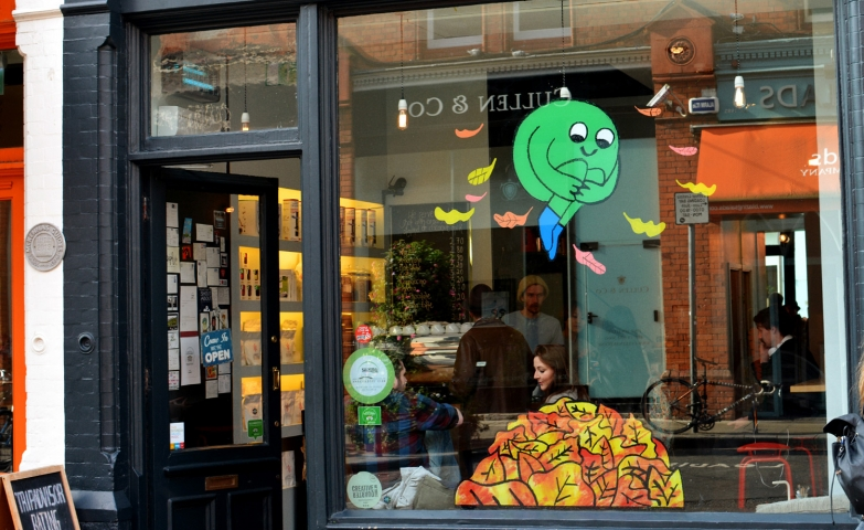 A cute sticker character jumping in stacks of leaves represents the autumn window display for this coffee shop.