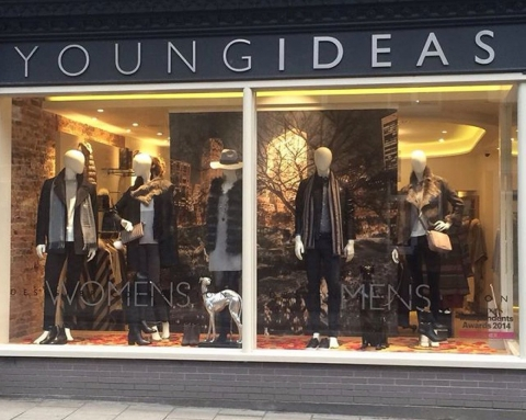 Young Ideas have dark colored clothes and a background with a tree without leaves for its autumn window display.
