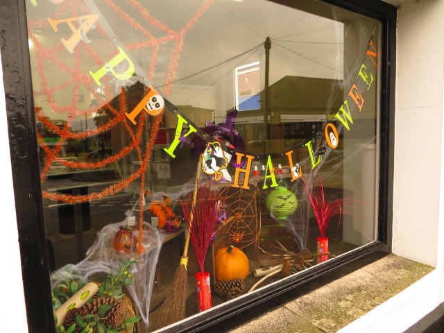 An easy way to decorate your Halloween window display is to hang a proper message on the window, add some pumpkins and it's all done.