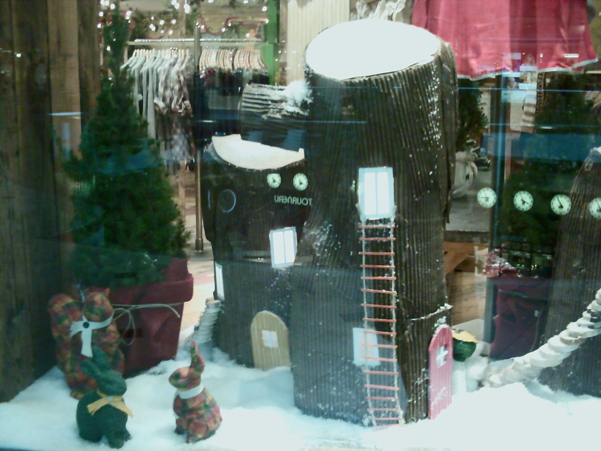 Something that looks like a place for living, specially created for those little bunnies, a fir in a flowerpot and a winter design in this window display.
