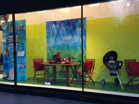 Classic summer design for a store which sells kitchen tools, window display decorated with backyard furniture and a grill for barbeque.