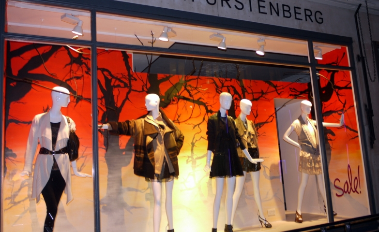 The autumn window display for Diane von Furstenberg store is designed with a sale dot and a creepy background.