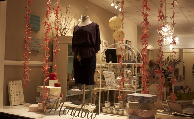 An autumn window display designed with a simple dress with a dark color and fallen leaves.