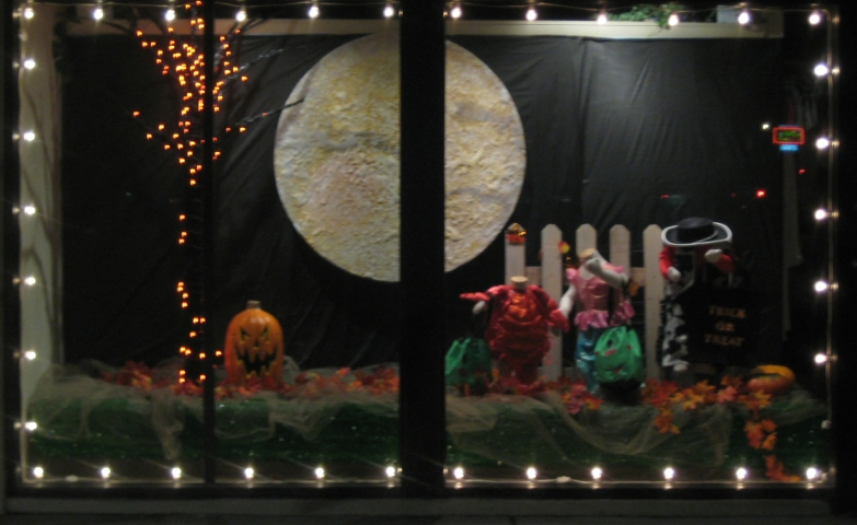 A black curtain on the back of the window display, a full moon for the Halloween night, a bad pumpkin and little costumes for little people.
