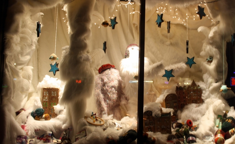 A furry winter wonderland situation with blue hanging stars and others little details that are creating a cute window display.
