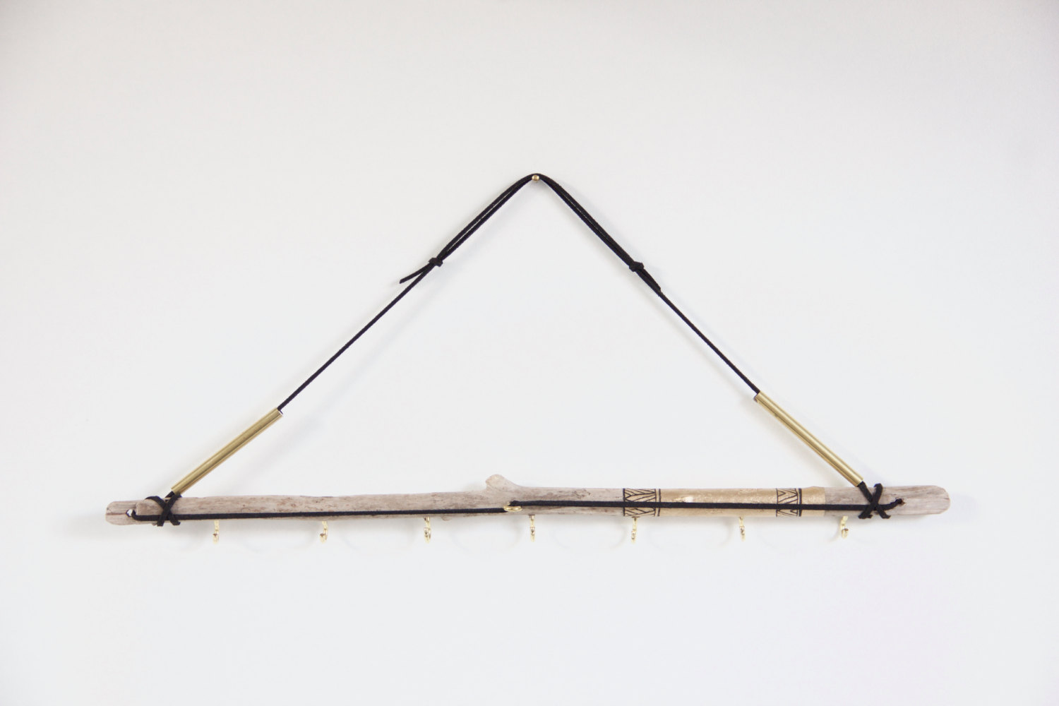 Creative and natural, this jewelry necklace holder made from driftwood and painted with gold has a minimalist air.