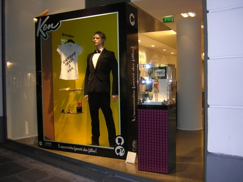 Ken is facing the autumn in a black costume, staying in a box with a yellow background, placed in a window display.