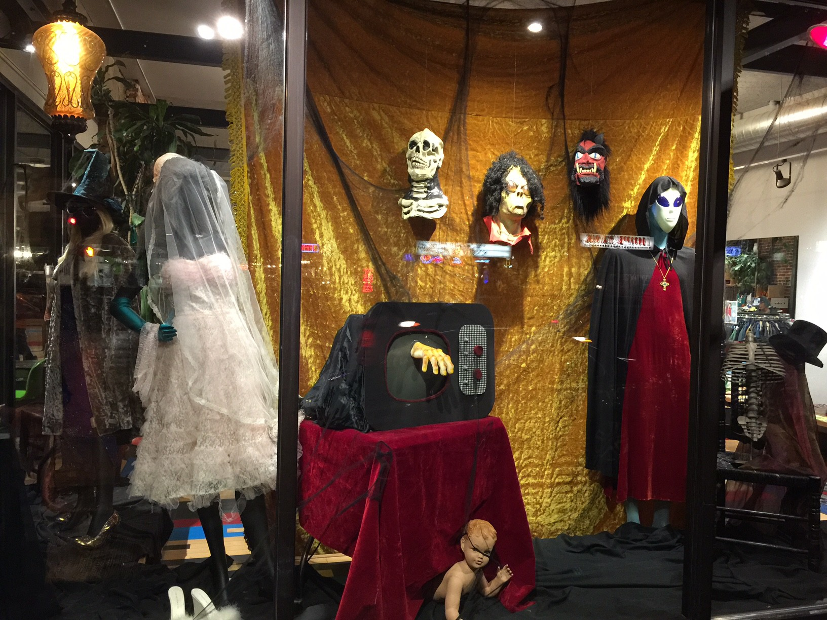 This golden curtain with hanging masks and a hand coming out from the tv, makes me think about a vintage style Halloween window display.