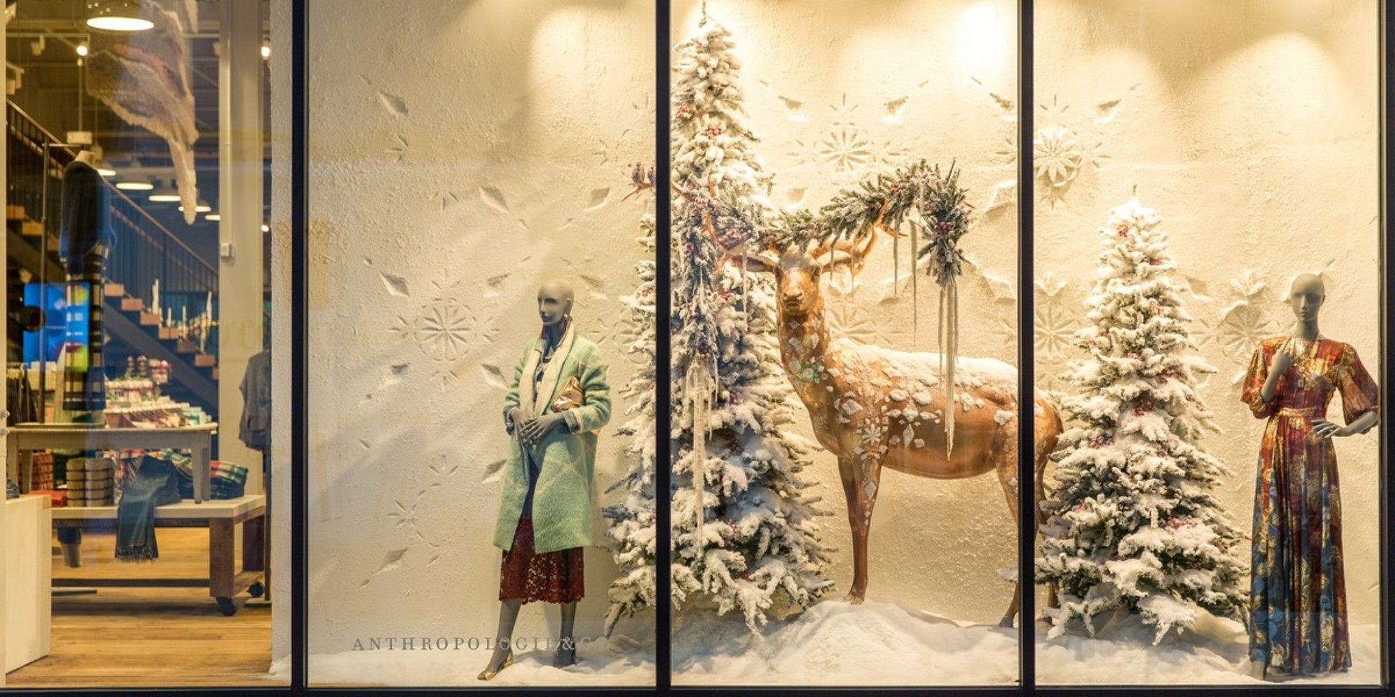 Very pretty scene with a golden reindeer between two snowed firs, and followed by two mannequins in a winter theme for this window display.
