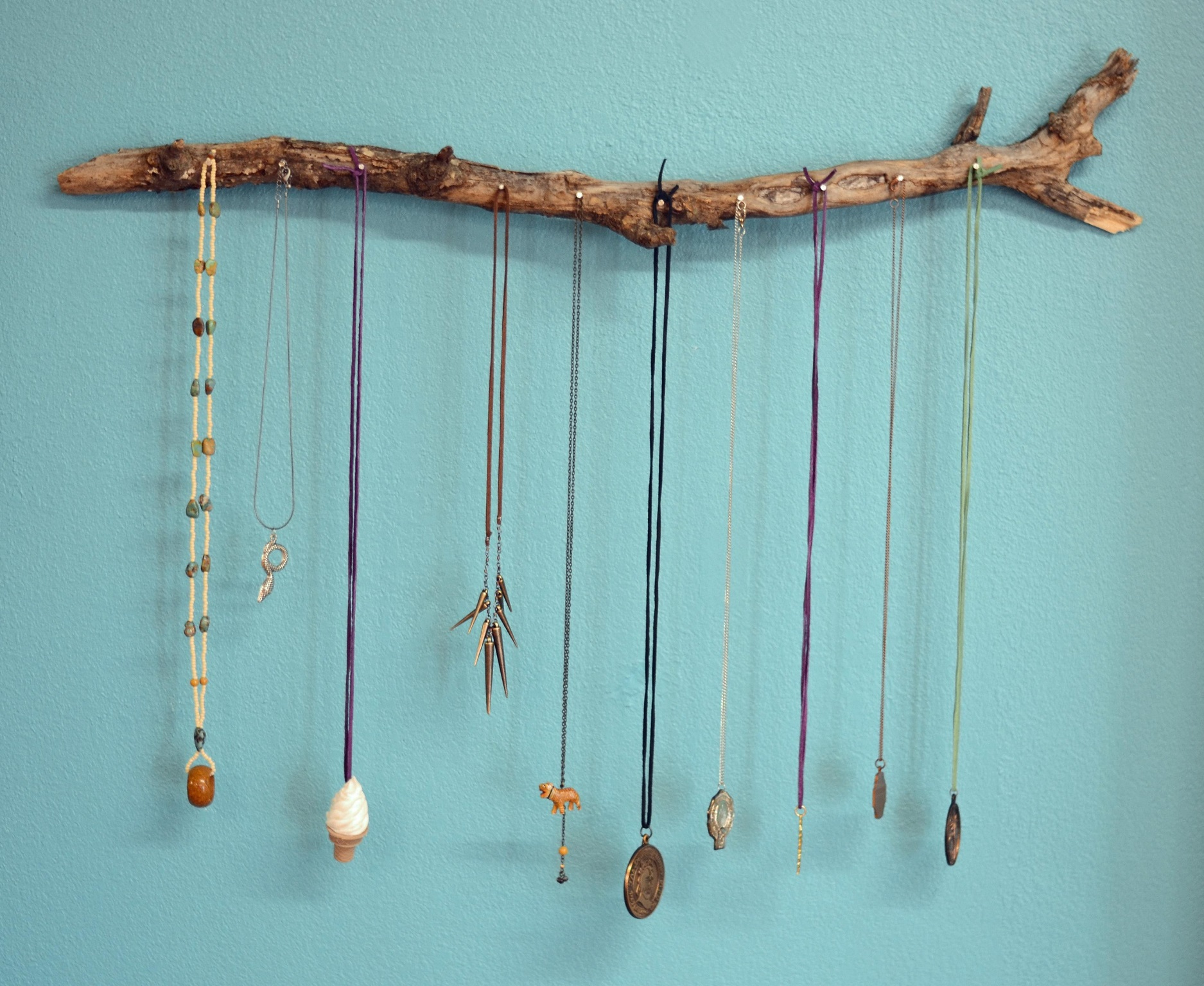 So easy to make a jewelry necklace holder in a creative way, by putting a few pins on a stick. You can choose a stick which has a twisted shape.