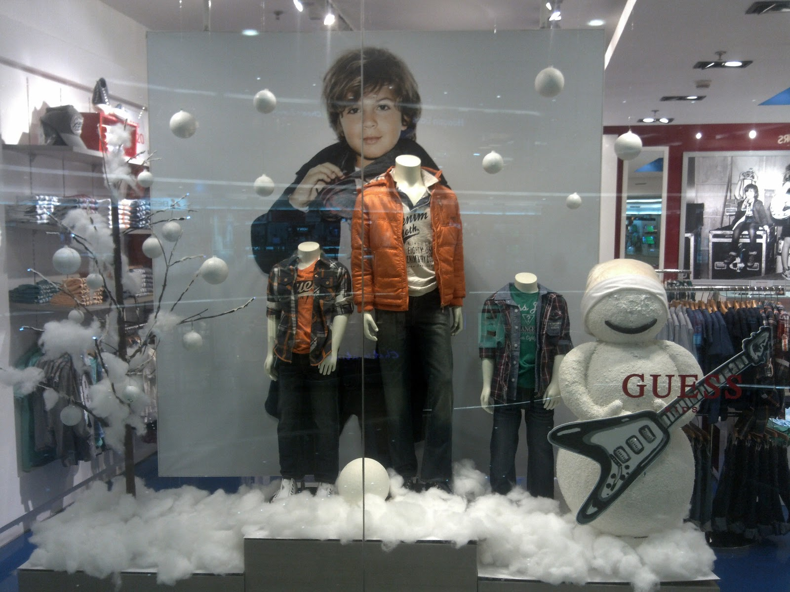 The winter window display for Guess kids has the main scene with a white situation, including a snowman and white pieces of cotton as snow.