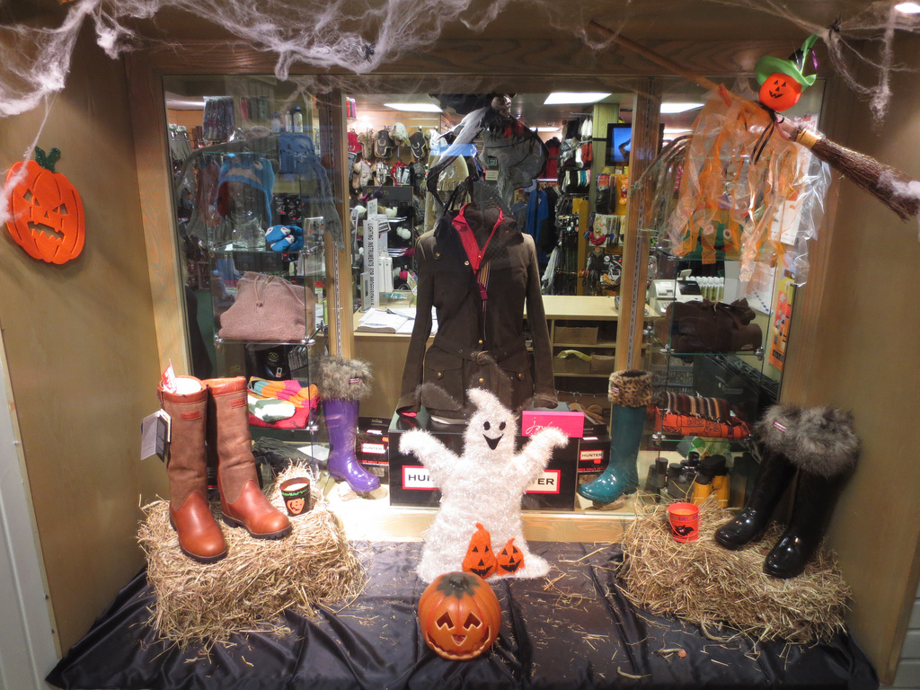 This window display surprises a Halloween scene with a happy ghost having some pumpkin prints on its coat and a pumpkin riding a broomstick.