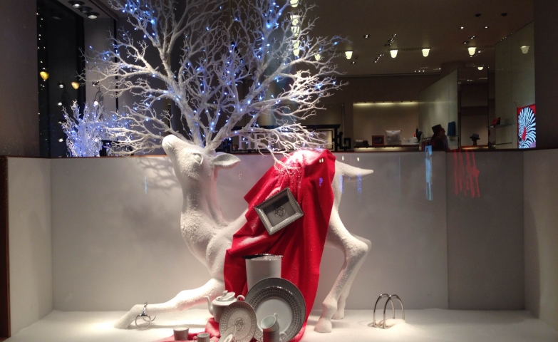 Hermes decorated the window display for winter, with a reindeer which has antlers transformed into a tree full of lights, also the reindeer has a red blanket on it and a dish falling down.