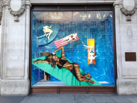A pool mirage, one good tan on a beautiful lady, creates a creative window display for H&M campaign.