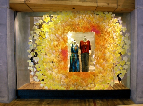 A store made a frame for their clothes out of autumn leaves to decorated the window display.