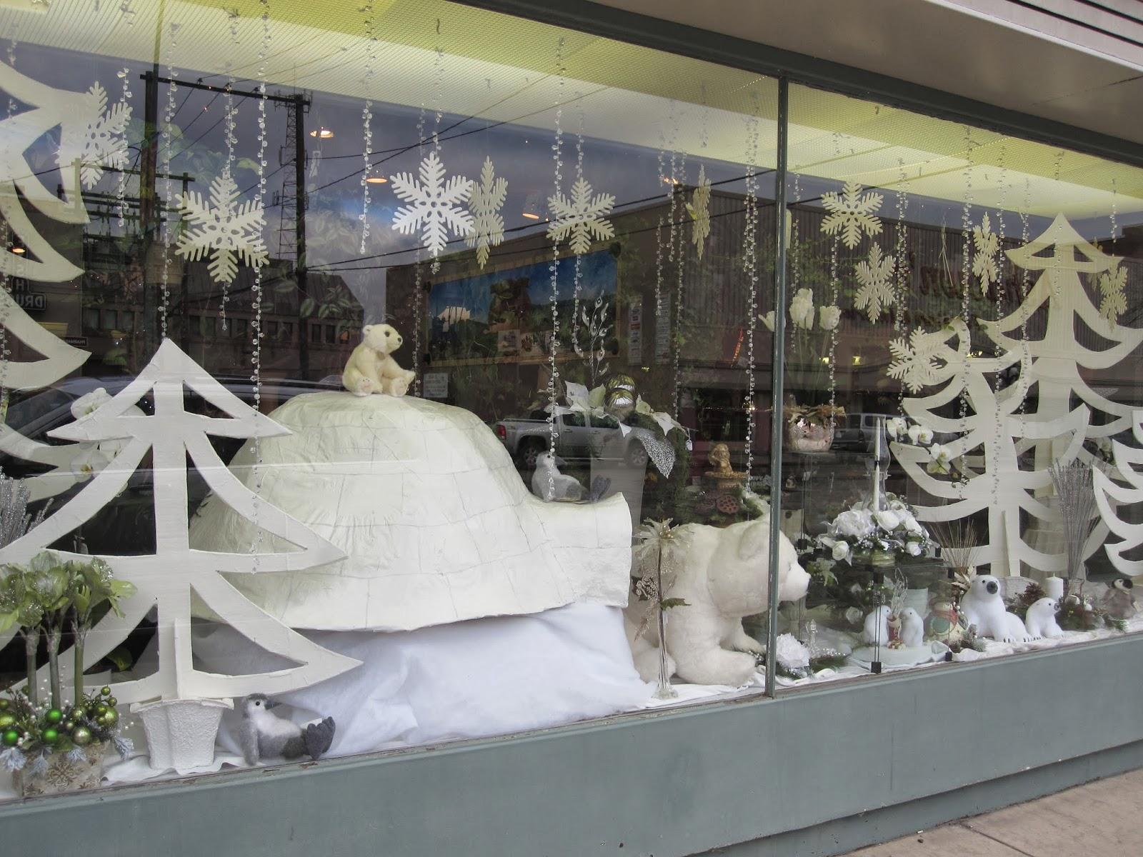 Winter window display, having some polar bears, an igloo and snowflakes hanging.
