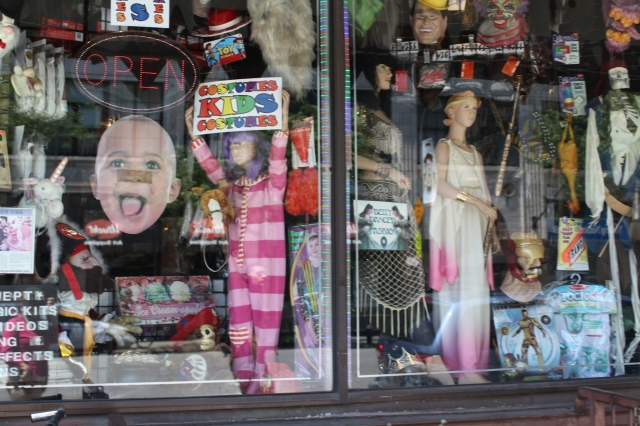 This Halloween window display has been decorated with costumes for kids and other accessories, making this look like a horror story, but not too horror.