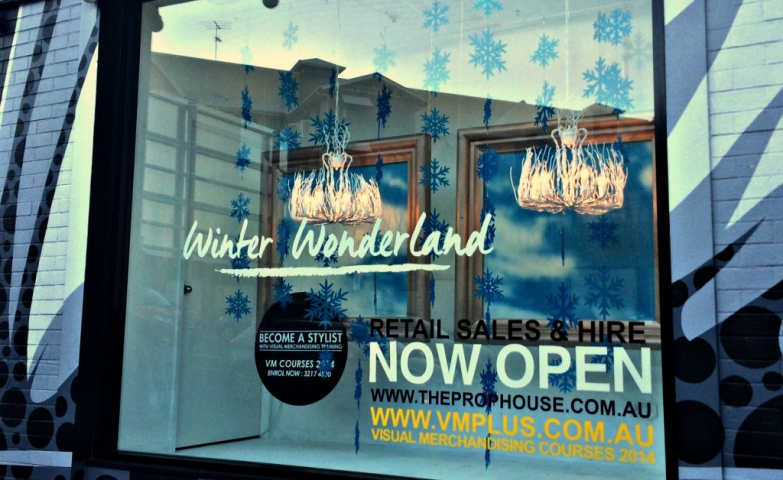 Winter window display with two others interior windows, hanging blue snowflakes and two chandeliers which seem on fire.