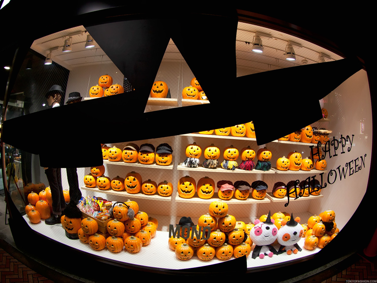 In Japan, a Halloween window display is decorated with two mannequins and lots of happy pumpkins.