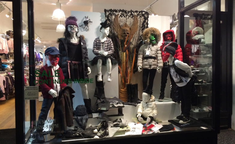 A window display showing kids mannequins celebrating Halloween and wearing scary masks for this.
