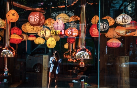 This autumn window display has a lot of hanging pendants in autumnal beautiful colors.