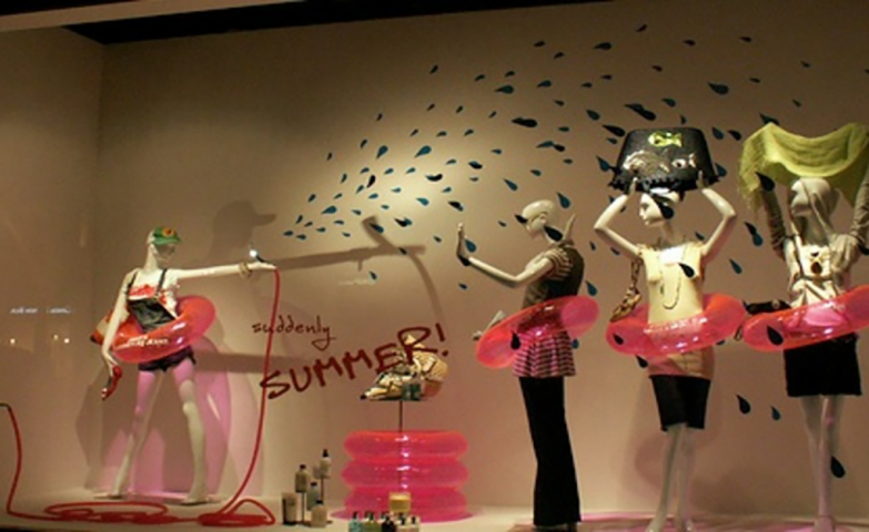 A simple summer window display with mannequins representing kids having fun