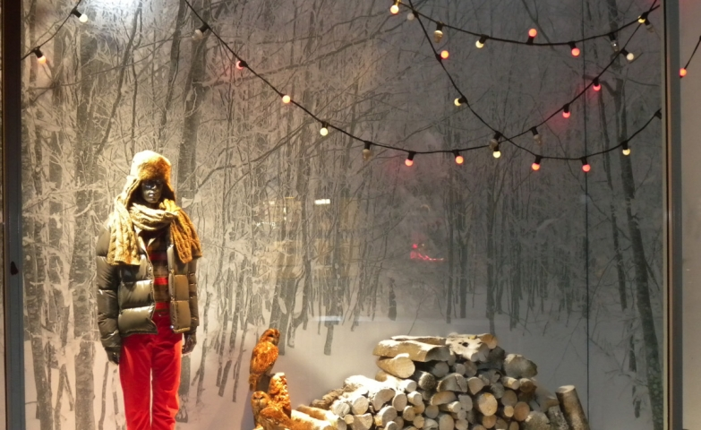 Wood for fire, a forest in the background and thick clothes on the mannequin, this is looking like a winter landscape all into the window display.
