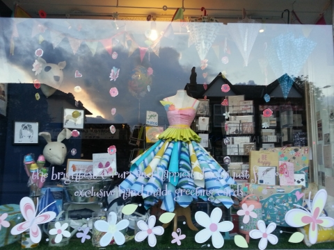 This window display has a light and airy vibe with flower and cards perfect for the summer