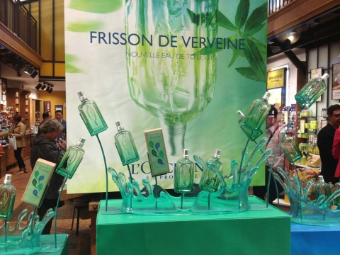 """L'Occitane promoted their eau de toilette """"dressed"""" with a green bottle in the window display, just in tone with summer."""
