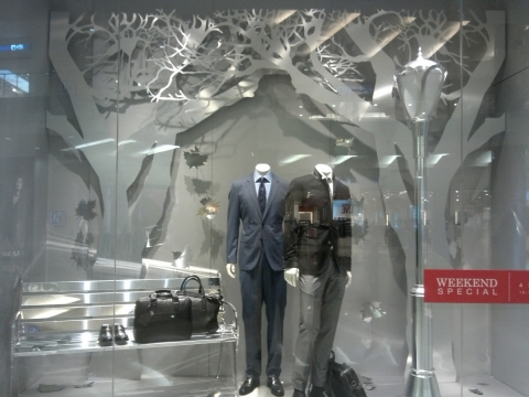 Hugo Boss made a simple but with effect autumn window display by decorating the background with white paper trees, a bench and a slim.