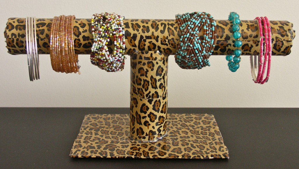 Bracelet holder in shape of T-letter, creative and practical. This is made of paperboard and animal print paper.