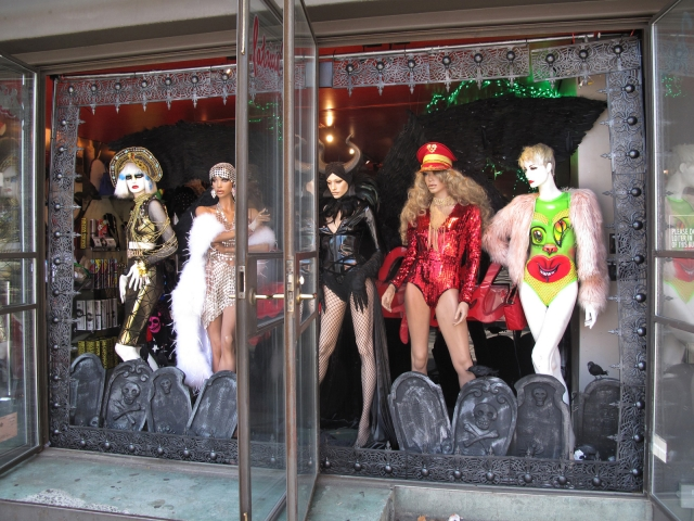 Mixed costumes between scary and fancy, representing a few characters, this Halloween window display has added some crypts in the below to look more horrific.