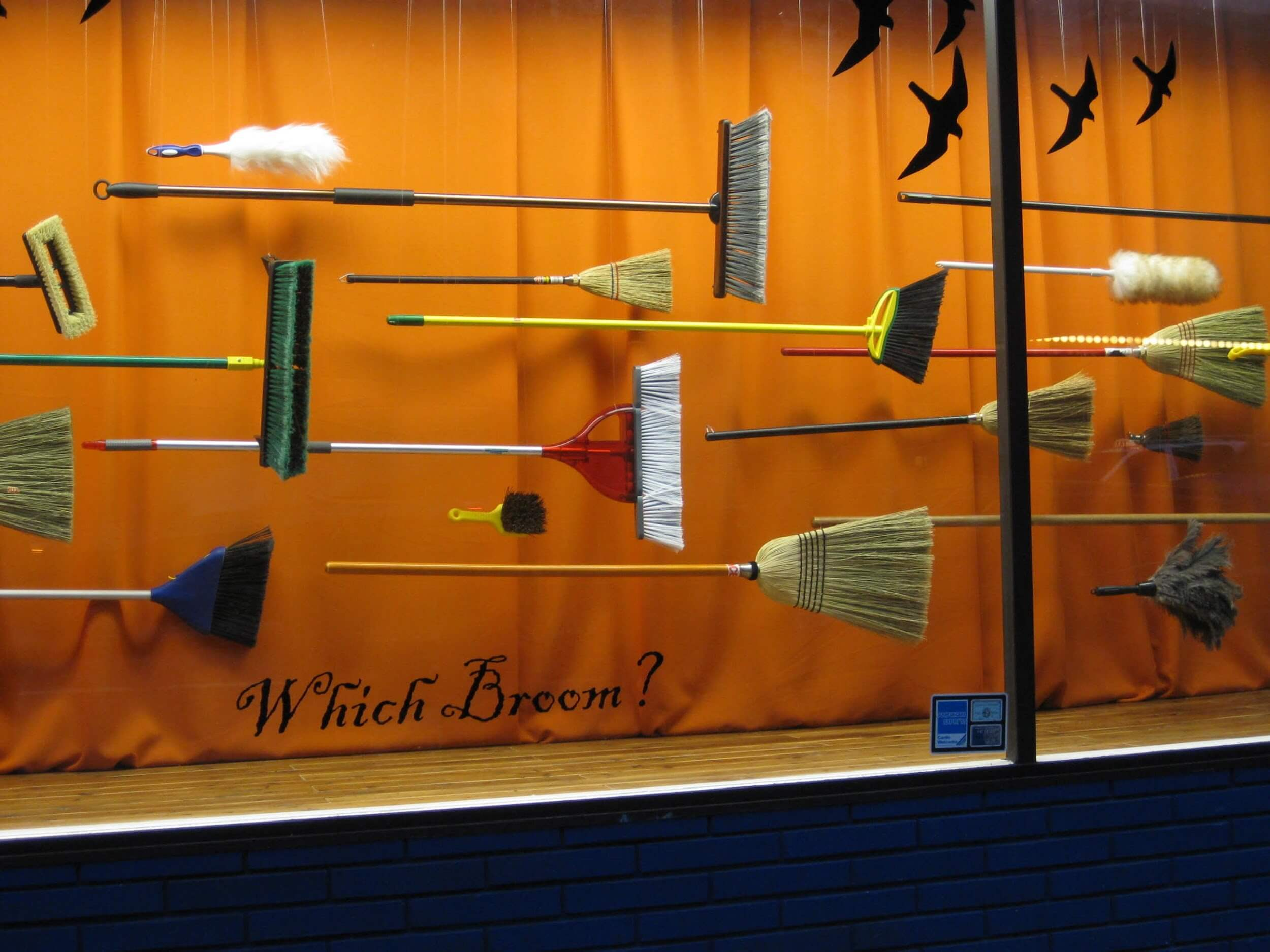 A creative Halloween window display with different models of broomsticks, an orange curtain and raven stickers.